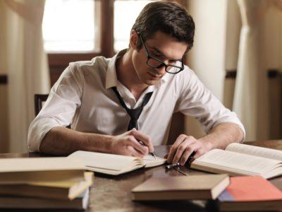 Un tânăr care stă la birou și scrie în agenda sa.